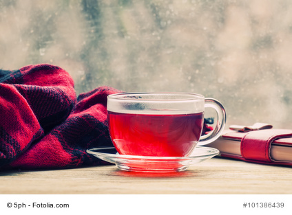 Cup with hot red tea in front of a window with water drops in ra